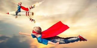 De kinderen in de vlieg van superherokostuums en tonen super capaciteiten stock fotografie
