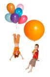De kinderen vliegen door ballons Stock Fotografie