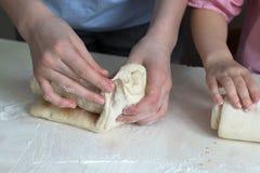 De kinderen vormen broodjes van deeg Keukenlijst in bloem Warme verhoudingenkinderen royalty-vrije stock fotografie