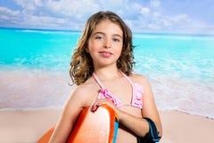 De kinderen vormen surfermeisje in tropisch turkoois strand Stock Afbeelding