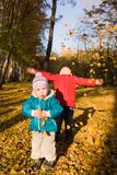 De kinderen werpen de herfstbladeren Royalty-vrije Stock Fotografie