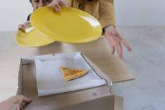 De kinderen worden gevraagd om hen het laatste stuk van pizza 4 te geven kazen die in de doos na een familiediner blijven stock fotografie