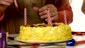 De kinderen zetten hun kaarsen in de verjaardagscake stock footage