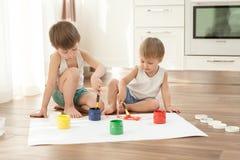 De kinderen zijn bezig geweest met creativiteit, zittend op de vloer stock afbeelding
