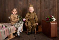De kinderen zijn gekleed in retro militaire uniformen die een militair sturen naar het leger, donkere houten achtergrond, retro s royalty-vrije stock afbeeldingen
