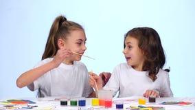 De kinderen zitten bij de lijst en schilderen zich op hun gezichten met verfborstels Witte achtergrond Langzame Motie stock video