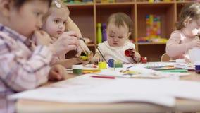 De kinderen zitten bij de lijst en trekken, trekt het kind in de voorgrond het gebruiken van rode teller, de kinderen op de achte stock videobeelden