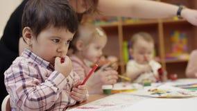 De kinderen zitten bij de lijst, het kind in de dichte mening die een rode teller houden, dan legt het terzijde en bereikt voor stock footage