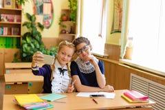 De kinderen zitten in de telefoons bij de lessen Stock Afbeeldingen