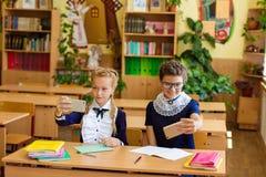 De kinderen zitten in de telefoons bij de lessen Stock Fotografie