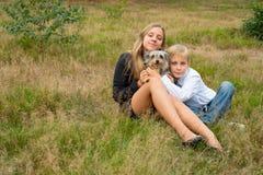 De kinderen zitten in het park met een hond stock fotografie