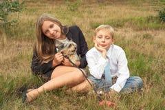 De kinderen zitten in het park met een hond royalty-vrije stock afbeelding