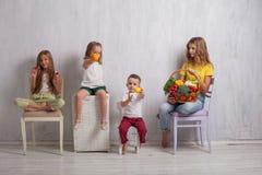 De kinderen zitten met verse groenten gezond het eten fruit stock foto's