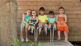 De kinderen zitten op de stoelen stock video