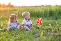 De kinderen zitten op het gras Stock Afbeeldingen
