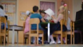 De kinderen zitten in de ruimte van de kinderen bij de lijst groepswerk groepswerk Geen duidelijkheid, geen nadruk stock footage