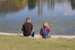 De kinderen zitten samen bij het meer en kijken uit aan het water stock fotografie
