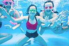 De kinderen zwemmen in pool stock foto's