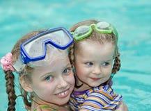 De kinderen zwemmen in zwembad. stock foto's