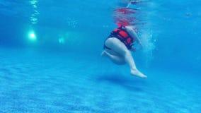 De kinderen zwemt in pool in het kader van water langzame motie stock video