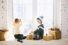 De kinderenbroer en de zuster van peuterleeftijd zitten door venster op een zonnige die Kerstmisdag en spelen met giftenvakjes in stock fotografie