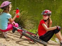 De kinderenfiets heeft rust dichtbij water in park openlucht Royalty-vrije Stock Foto