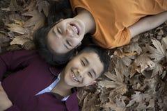 De kinderengezichten van Similing in de bladeren Stock Fotografie