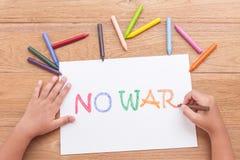 De kinderenhand schrijft GEEN OORLOG in Witboek met cray kleur Stock Afbeeldingen