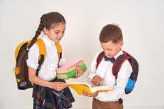 De kinderenjongen en de studentes communiceren op school het meisje helpt de jongen om de schooltaak in het handboek te demontere stock foto