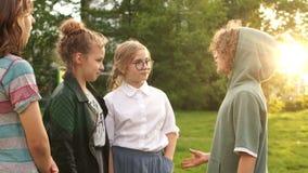 De kinderenklasgenoten spreken aan elkaar tijdens een gang in het park, schoolvriendschap, terug naar school Zonsondergang, lins  stock video