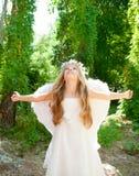 De kinderenmeisje van de engel in bos witte vleugels stock foto