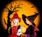 De kinderenmeisjes van Halloween met boom en knuppels Stock Fotografie