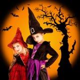 De kinderenmeisjes van Halloween met boom en knuppels Stock Foto