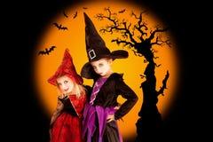 De kinderenmeisjes van Halloween met boom en knuppels Stock Foto's