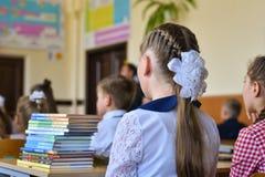 De kinderenschoolkinderen zitten bij hun bureaus in het klaslokaal van de school, het begin van het schooljaar, 1 September stock afbeelding