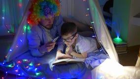 De kinderensprookjes, gebaarde mensen in clownpruik met zoon lezen boek in verlichting van flitslicht in tent met slingers stock footage