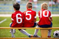 De kinderenteam van het voetbalvoetbal De spelers die van het jonge geitjessubstituut op een bank zitten royalty-vrije stock afbeeldingen