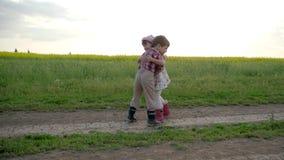 De kinderenvrienden die elkaar koesteren, die rond gelukkige gebiedsweg, langzame motie, jongen en meisje lopen komen, het mooie  stock footage