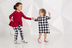 De kinderenzusters spelen samen op witte achtergrond Stock Afbeelding