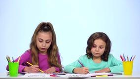 De kinderenzusters, verfraaien het beeld met potloden Witte achtergrond Langzame Motie stock footage