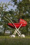 De kinderwagen van het stuk speelgoed in boomgaard Royalty-vrije Stock Afbeeldingen