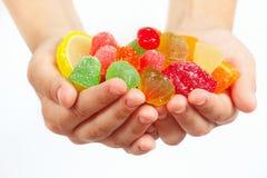 De kindhanden met kleurrijke fruitige snoepjes en de gelei sluiten omhoog Stock Foto