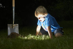 De kindjongen heeft een schat in het gras ontgraven Royalty-vrije Stock Foto