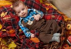 De kindjongen ligt op geruit Schots wollen stofplaid met gele de herfstbladeren, appelen, pompoen en decoratie, dalingsseizoen Royalty-vrije Stock Foto