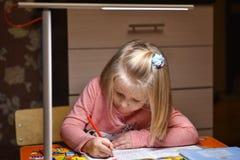 De kindkleuter leert om in notitieboekjes thuis in de avond onder het licht van een bureaulamp te trekken en te schrijven stock afbeelding