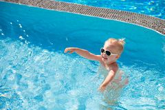 De kindplonsen in de pool stock fotografie