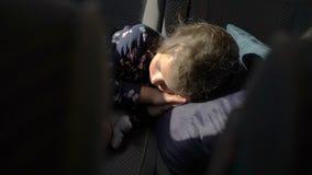 De kindslaap in de achterbank van de auto