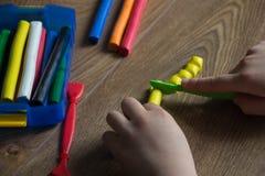 De kindspelen in een multi-colored plasticine op een houten lijst Creatief met kinderen stock afbeeldingen