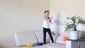 De kindspelen met de ballen van spoelen van draad stock footage