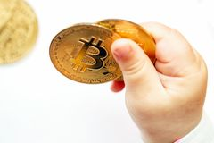 De kindspelen met cryptocurrency Bitcoinmuntstuk in babyhanden Close-up stock foto